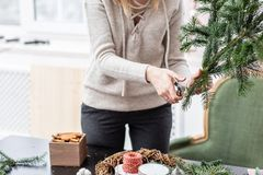 Manufacturer of Christmas wreath from branches of pine for holiday. Master class on making decorative ornaments. Christmas decor with their own hands. The new stock photo