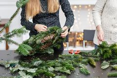 Manufacturer of Christmas wreath from branches of pine for holiday. Master class on making decorative ornaments. Christmas decor with their own hands. The new stock images