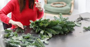 Manufacturer of Christmas wreath from branches of pine for holiday. Master class on making decorative ornaments. Christmas decor with their own hands. The new royalty free stock photography
