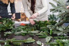 Manufacturer of Christmas wreath from branches of pine for holiday. Master class on making decorative ornaments. Christmas decor with their own hands. The new royalty free stock images