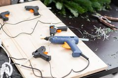 Several glue guns in the foreground on the Board. Manufacturer of Christmas wreath from branches of pine for holiday. Manufacturer of Christmas wreath from stock photography