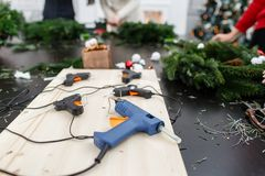 Several glue guns in the foreground on the Board. Manufacturer of Christmas wreath from branches of pine for holiday. Manufacturer of Christmas wreath from stock photo