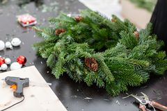 Manufacturer of Christmas wreath from branches of pine for holiday. Master class on making decorative ornaments. Christmas decor with their own hands. The new stock image