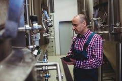 Manufacturer examining machinery at brewery Stock Photos