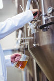Manufacturer filling beer into glass at brewery Stock Photo