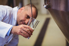 Manufacturer filling beer into glass at brewery Royalty Free Stock Photos