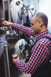 Manufacturer filling beer from storage tank at distillery. Manufacturer filling beer into glass from storage tank at distillery royalty free stock photography