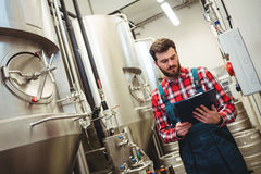 Manufacturer holding writing pad in brewery Stock Photo