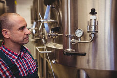 Manufacturer looking at pressure gauge in brewery Stock Image