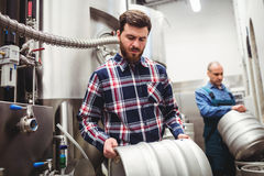 Manufacturer and worker lifting kegs Royalty Free Stock Image