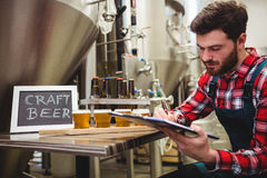 Manufacturer writing on writing pad in brewery Stock Images