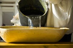 Manufacturing handmade paper. Pouring water in a vintage wooden tray with cellulose in it stock images