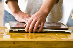 Manufacturing handmade paper. Hands squeezing the cellulose between two wooden plates Stock Images
