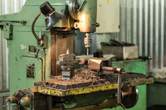 Manufacturing of parts on a drill press. Metal, drilling holes. Royalty Free Stock Image