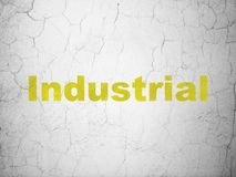 Manufacuring concept: Industrial on wall background. Manufacuring concept: Yellow Industrial on textured concrete wall background Stock Photos