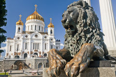 Manument reclining lion with Cathedral. Manument reclining lion with Christ the Savior Cathedral in Moscow Stock Image