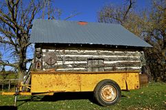 Manure spreader in front of an old log cabin Royalty Free Stock Image