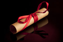 Manuscript roll. Rolled manuscript tied red ribbon on dark backgroung stock photos