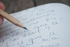 Manuscript writing closeup. Wooden pen on the manuscript writing closeup Royalty Free Stock Image