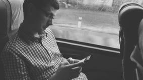 manusing一个手机的年轻人检查在他的电子邮件通勤对工作乘在一次长的旅行的公共汽车 影视素材