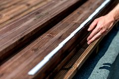 Manusje van alles die houten bevloering installeren in terras, die met boor werken royalty-vrije stock foto's