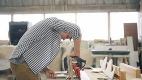 Manusje van alles scherp hout die met figuurzaag elektrisch instrument in workshop gebruiken stock videobeelden