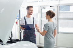A manutenção de sorriso projeta a agitação das mãos com o cliente fêmea na oficina de reparações do carro Imagem de Stock