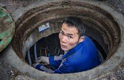 Manutenção de trabalhadores subterrâneos do encanamento Fotografia de Stock