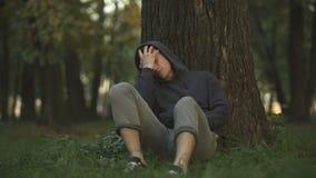 Manutenção insalubre do homem no parque, sentando-se sob a árvore após o bom partido, doença vídeos de arquivo