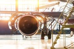Manutenzione aperta del getto del motore dell'aeroplano del cappuccio nelle scale del capannone, con il chiarore della luce inten fotografia stock