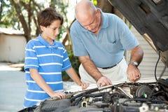 Manutenzione dell'auto del figlio e del padre immagine stock