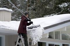 Manutenzione domestica di inverno - rimozione di neve del tetto immagini stock