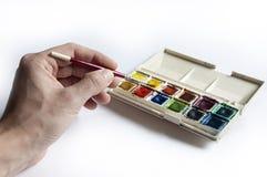 Manvänstersidahand genom att använda vattenfärguppsättningen med målarpenseln Royaltyfri Foto