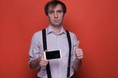 Manvisningsmartphone med den tomma skärmen och att tumma upp fotografering för bildbyråer