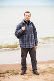 Manwith backpack stands on Sea coast. Traveler on Baltic Sea coast. Young adult  Caucasian man in warm outdoor clothes with backpack stands on empty sandy beach Stock Image