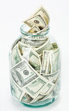 Many 100 US dollars bank notes in a glass jar. Isolated  on white background Royalty Free Stock Photography