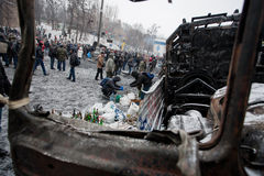 Many active people walk around the winter snowy street with burned cars and buses during anti-government protest Euromaidan Royalty Free Stock Photos