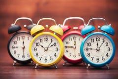 Many alarm clocks on wooden table Stock Photo