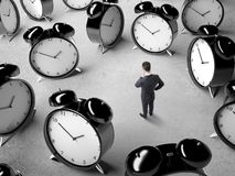 Many alarms. Businessman standing and thinking among many alarms stock photos