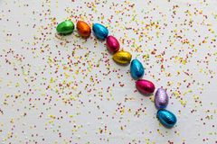 Many aligned colored chocolate easter eggs on white background and colorful confetti royalty free stock photography