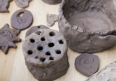 Many amateur handmade unbaked clay moldings. On a wooden table stock images