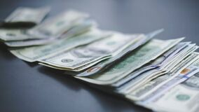 Many American dollars are slowly falling onto the table. Man throws green american money. American financial system