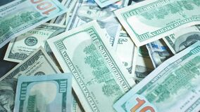Many american dollars are spinning. Green American money is on the table. American financial system. Rotating background