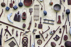 Many ancient farming tools hanging on the wall of the rural Hous Stock Photography