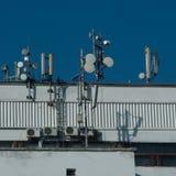 Many antennas on city building. Antennes GSM 3G CDMA UMTS. Many antennas on city building. Antennes GSM 3G CDMA UMTS against the blue sky Stock Photo