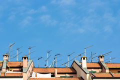Many antennas installed on the roof of a building stock image