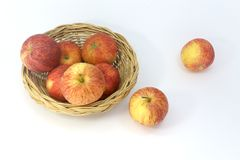 Many apples in the basket isolated on white background. Two apples outside the basket royalty free stock images
