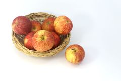 Many apples in the basket isolated on white background. One apples outside the basket royalty free stock photo