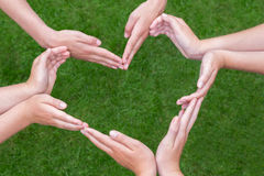 Many arms of children construct heart above grass Royalty Free Stock Image