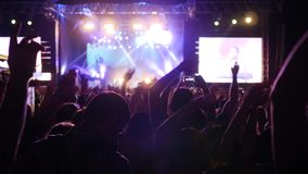 Many arms raised of fans in bright lights of stage, crowd of people waving arms and hold phone with digital displays